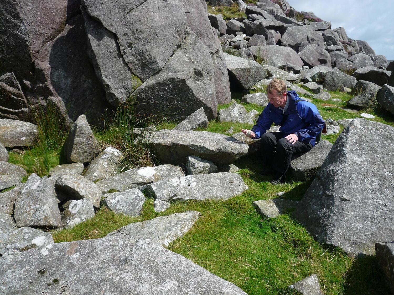 Man crouching amid rocks
