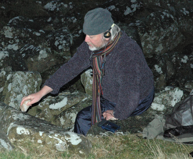 Man with headphones striking a rock